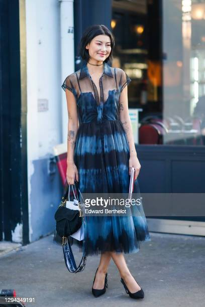 Guest wears a Dior necklace, a tie-and-dye tulle mid-length dress, a black Dior saddle bag, black Dior pumps , outside Dior, during Paris Fashion...