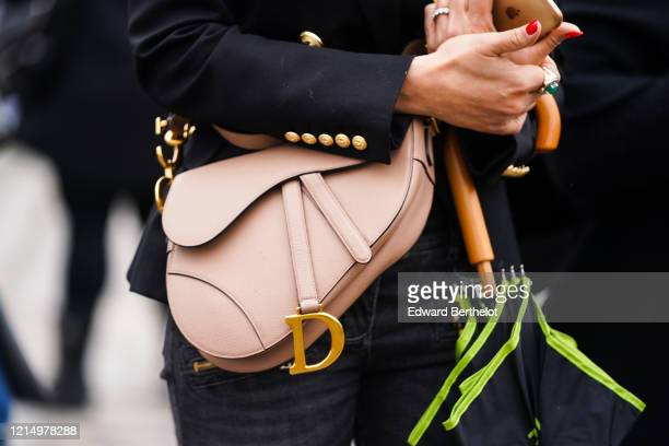 Guest wears a Dior nude-color Saddle bag, outside Balmain, during Paris Fashion Week - Womenswear Fall/Winter 2020/2021, on February 28, 2020 in...
