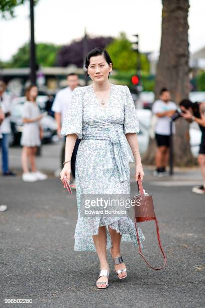A guest wears a dress with blue flower prints silver shoes a brown leather bag outside Vetements during Paris Fashion Week Haute Couture Fall Winter...