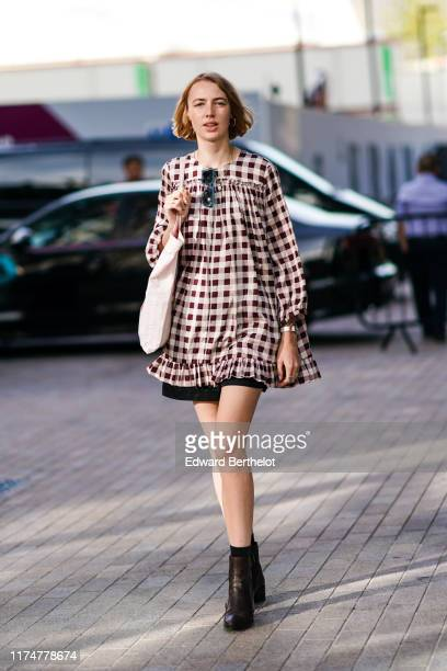Guest wears a dress with checked gingham pattern print, a tote bag, black leather shoes, sunglasses, during London Fashion Week September 2019 on...