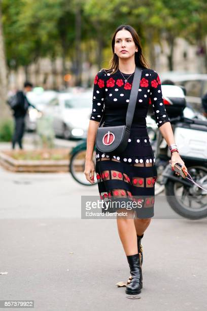 A guest wears a dress with embroidered flowers a leather bag outside Shiatzy Chen during Paris Fashion Week Womenswear Spring/Summer 2018 on October...