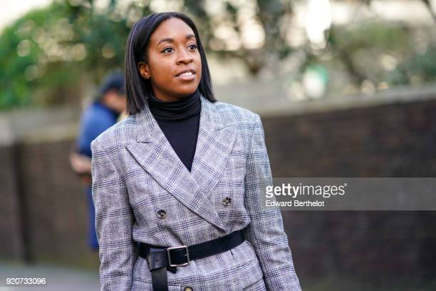 Guest wears a fabric pattern blazer gray jacket, a black turtleneck top, a belt, during London Fashion Week February 2018 on February 17, 2018 in...