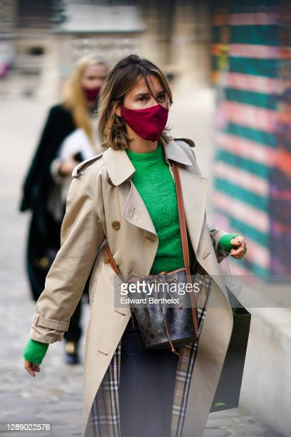 Guest wears a face mask, a green wool pullover, a Burberry beige trench coat with checked inner lining, a brown leather bag with printed patterns,...