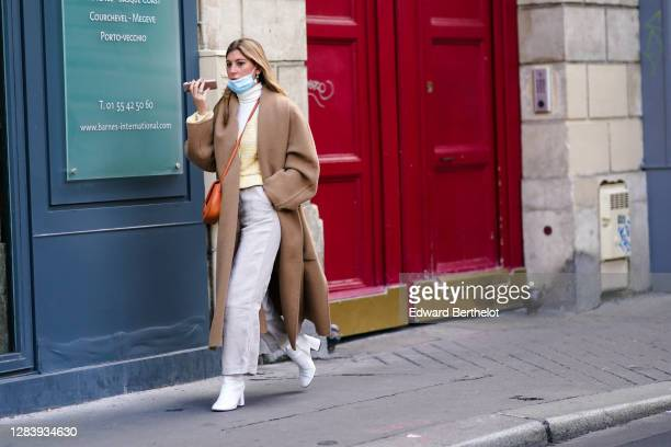 Guest wears a face mask, a turtleneck wool pullover, a pale brown / beige long wool coat, gray pants, white pointy high heeled boots, a brown leather...