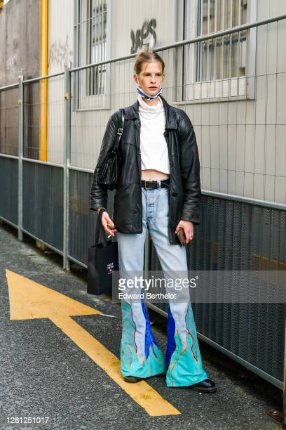 A guest wears a face mask a white cropped top a black leather jacket blue and green / turquoise flared denim jeans pants a leather belt holds a...