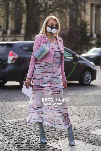 A guest wears a face mask with embroidered white flowers a pale blue Chanel quilted bag a pink jacket a flowing ruffled dress with printed geometric...