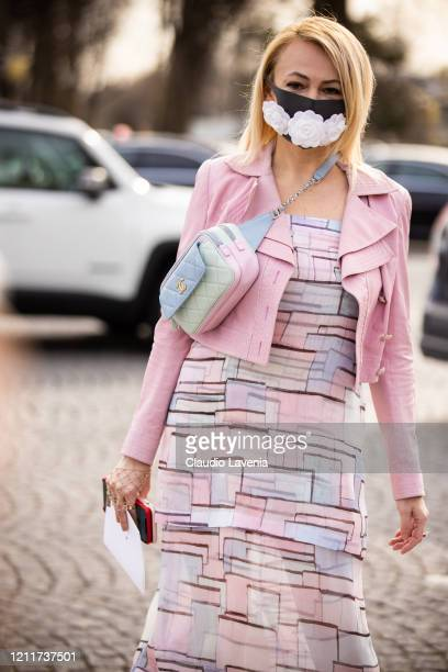 Guest wears a face mask with embroidered white flowers, a pale blue Chanel quilted bag, a pink jacket a flowing ruffled dress with printed geometric...
