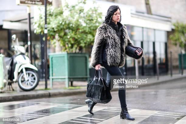 A guest wears a faux fur coat a black bag denim jeans pants and black boots outside the JOUR/NE show during Paris Fashion Week Womenswear Fall/Winter...