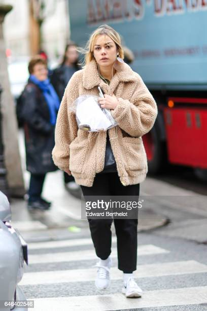 A guest wears a faux fur coat black pants and white shoes outside the JOUR/NE show during Paris Fashion Week Womenswear Fall/Winter 2017/2018 on...
