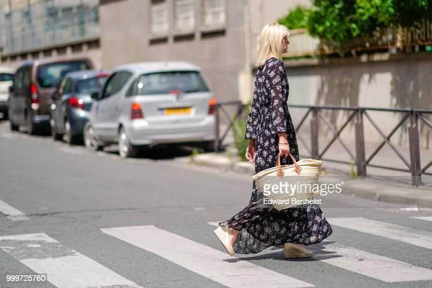 A guest wears a floral print dress a basket bag outside Wooyoungmi during Paris Fashion Week Menswear SpringSummer 2019 on June 23 2018 in Paris...