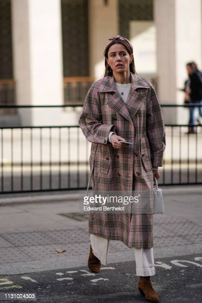 Guest wears a floral print headband, a white sweater, a brown and pink Prince of Wales check trench coat, a white handbag, white wide-leg cuffed...