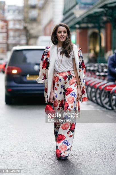 A guest wears a floral print jacket a white top a necklace flare pants a red bag during London Fashion Week February 2019 on February 18 2019 in...