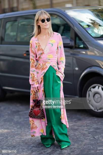A guest wears a floral print kimono dress green pants outside Nina Ricci during Paris Fashion Week Womenswear Spring/Summer 2018 on September 29 2017...