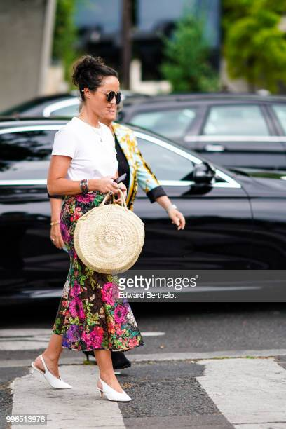 A guest wears a floral print multicolor skirt a star circular bag outside Vetements during Paris Fashion Week Haute Couture Fall Winter 2018/2019 on...