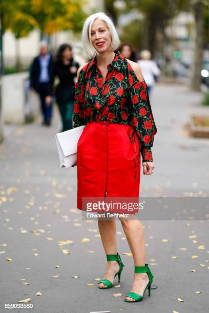 A guest wears a floral print off shoulder shirt a red skirt green heels shoes a bag outside Andrew GN during Paris Fashion Week Womenswear...