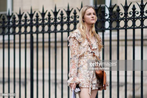 A guest wears a floral print ruffled dress white thigh high boots a brown fringed bag outside JeanPaul Gaultier during Paris Fashion Week Haute...