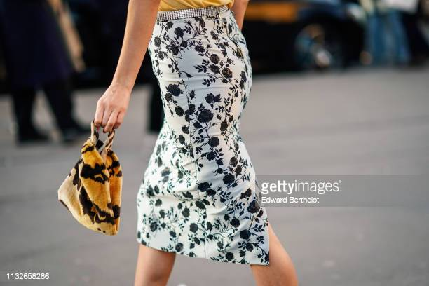 Guest wears a floral print skirt, a black and yellow bag, outside Rochas, during Paris Fashion Week Womenswear Fall/Winter 2019/2020, on February 27,...