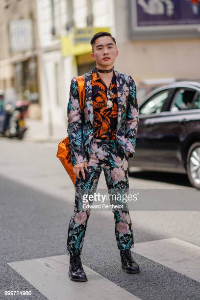 A guest wears a flower print blazer jacket floral print pants black leather shoes and orange and black shirt a choker outside Wooyoungmi during Paris...