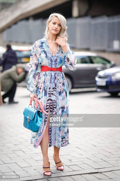 A guest wears a flower print dress a red belt a blue bag shoes during London Fashion Week February 2018 on February 18 2018 in London England