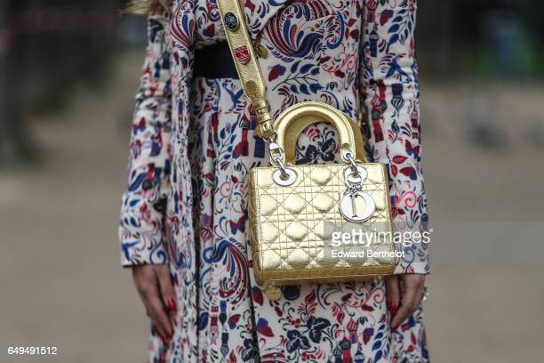 A guest wears a flower print dress and a gold Dior bag outside the Moncler show during Paris Fashion Week Womenswear Fall/Winter 2017/2018 on March 7...