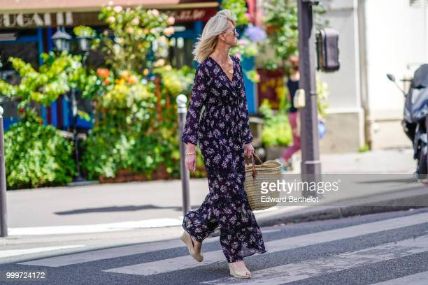 A guest wears a flower print dress and white shoes a straw bag outside Wooyoungmi during Paris Fashion Week Menswear SpringSummer 2019 on June 23...