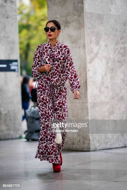 A guest wears a flower print dress outside the Lemaire show during Paris Fashion Week Womenswear Spring/Summer 2018 on September 27 2017 in Paris...