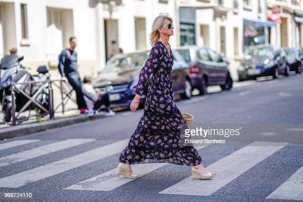 A guest wears a flower print dress white shoes outside Wooyoungmi during Paris Fashion Week Menswear SpringSummer 2019 on June 23 2018 in Paris France