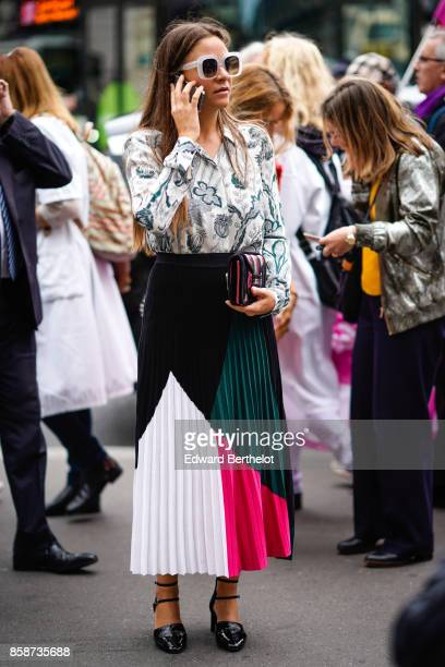 A guest wears a flower print shirt a pleated color skirt uses a smartphone outside Stella Mccartney during Paris Fashion Week Womenswear...