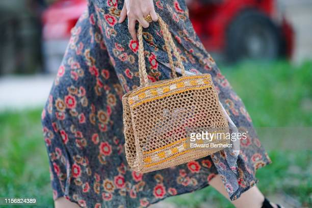 Guest wears a flowing floral print blue skirt, a straw woven bag, outside AMI, during Paris Fashion Week - Menswear Spring/Summer 2020, on June 18,...