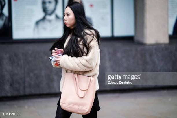 A guest wears a fluffy beige jacket a pale pink tote bag during London Fashion Week February 2019 on February 19 2019 in London England