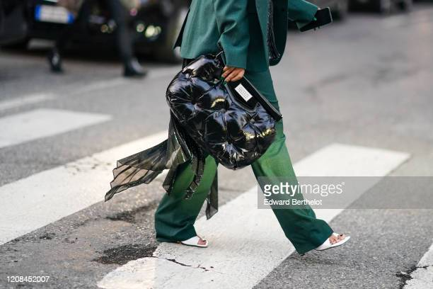 Guest wears a forest-green pantsuit with full-length pants, a shiny black Maison Margiela quilted clutch, white sandals, outside Bottega Veneta,...