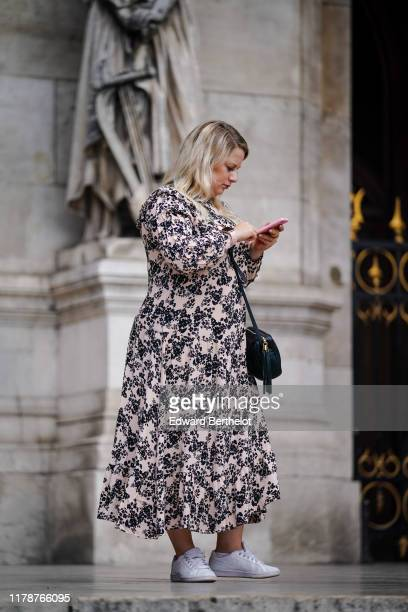 Guest wears a frilly collar light pink long gathered dress with black floral print, a black bag, white Nike sneakers, outside Stella McCartney ,...