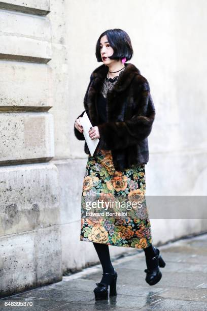 A guest wears a fur coat and a floral print skirt outside the JOUR/NE show during Paris Fashion Week Womenswear Fall/Winter 2017/2018 on February 28...