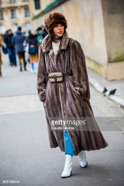A guest wears a fur coat Gucci bag and white hells boots in the streets of Paris after the Dior show during Paris Fashion Week Womenswear Fall/Winter...