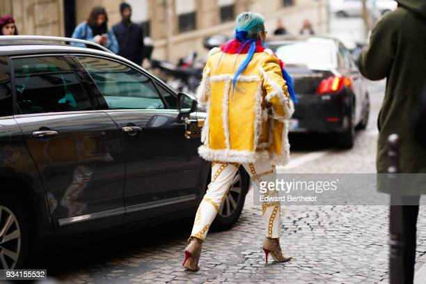 A guest wears a furlined yellow leather jump jacket gold chains pattern white pants taupe studded pointy toe highheeled booties during Paris Fashion...