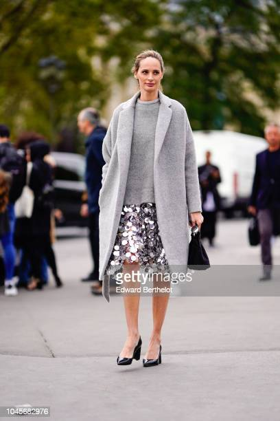 A guest wears a gary coat a silver sequin skirt outside Chanel during Paris Fashion Week Womenswear Spring/Summer 2019 on October 2 2018 in Paris...