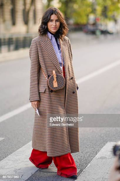 A guest wears a gingham checkered coat a Vuitton bag outside Thom Browne during Paris Fashion Week Womenswear Spring/Summer 2018 on October 3 2017 in...