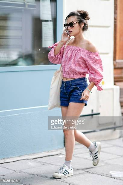 A guest wears a gingham vicht offshoulder bare belly top blue denim short adidas sneakers shoes sunglasses outside the Dries Van Noten show during...