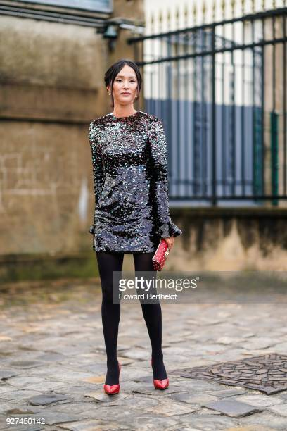 A guest wears a glitter dress a red bag black tights red shoes outside Valentino during Paris Fashion Week Womenswear Fall/Winter 2018/2019 on March...