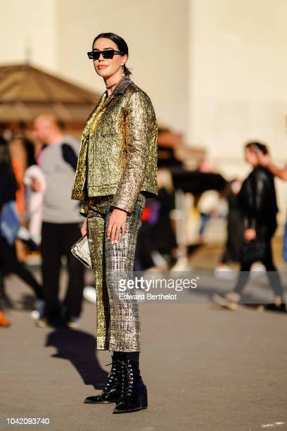A guest wears a glitter golden jacket flare pants black boots sunglasses outside Rochas during Paris Fashion Week Womenswear Spring/Summer 2019 on...