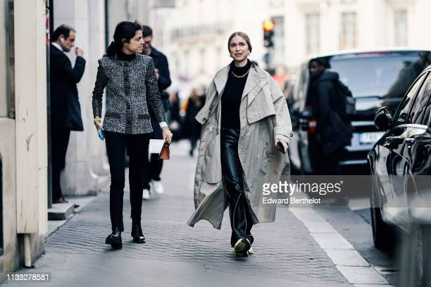 A guest wears a glittering grey jacket black pants black shoes Pernille Teisbaek wears earrings a necklace a black turtleneck a grey oversize trench...