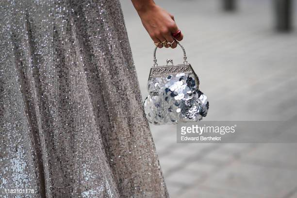 Guest wears a glittering sequined silver skirt, a glittering silver sequined minaudiere, outside Guy Laroche, during Paris Fashion Week - Womenswear...