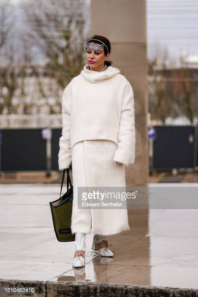A guest wears a glittering tiara a fluffy creamcolor oversized sweater with a cowl neck a matched wrapskirt a khaki Gianni Chiarini shopping bag...