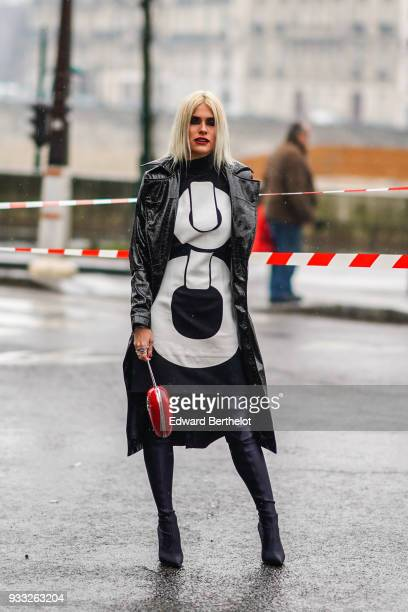 80ad4ae92ef5 A guest wears a glossy black vinyl trenchcoat a black dress with large  white pattern a