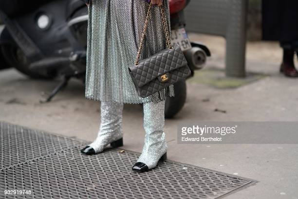 A guest wears a glossy silver grey flowy pleated midi skirt glossy silver boots with black patent square toe a grey Chanel handbag during Paris...