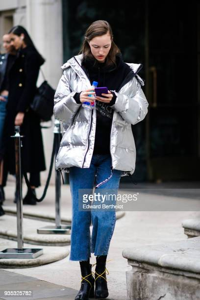 A guest wears a glossy silver puffy jacket blue denim ripped and wideleg crop pants black boots during London Fashion Week February 2018 on February...
