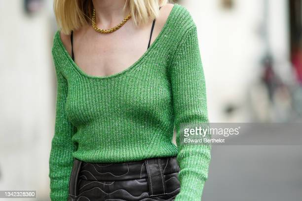 Guest wears a gold chain necklace, a green ribbed wool long sleeves pullover, a black shiny leather embroidered pattern short skirt, outside the Max...