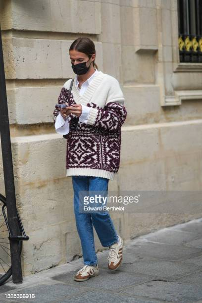 Guest wears a gold chain necklace, a white shirt, a white wool V-neck with burgundy embroideries oversized pullover, a black leather Chanel shoulder...