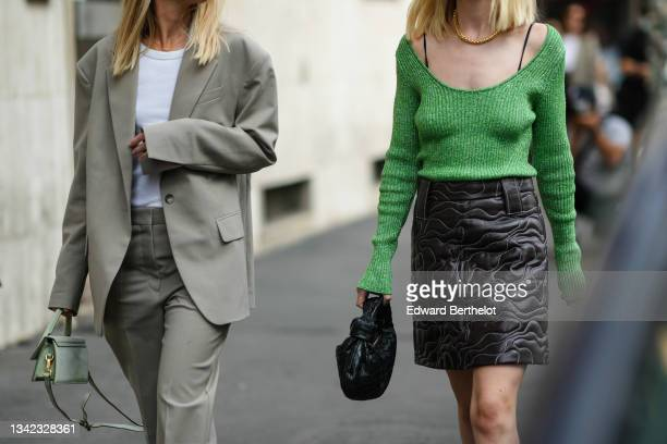 Guest wears a gold chain necklace, a white t-shirt, a pale gray long oversized blazer jacket, matching pale gray suit pants, a pale green suede...