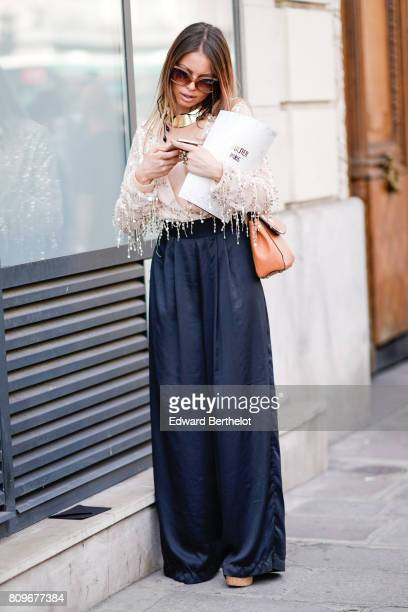 A guest wears a gold choker a white lace fringed top dark blue large pants and orange bag outside the Jean Paul Gaultier show during Paris Fashion...